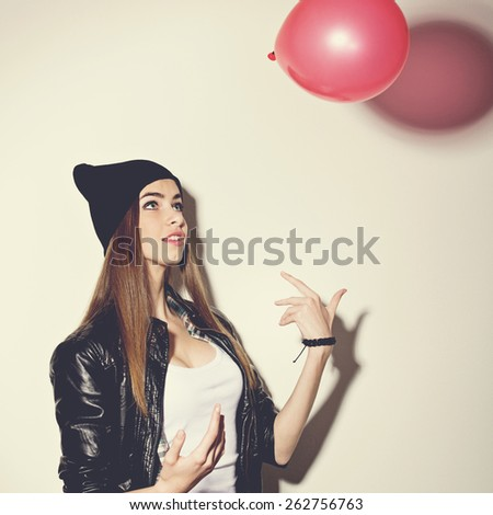 Closeup studio shot of beautiful hipster fashionable teenage girl with red balloon wearing black leather jacket and black beanie hat. Square format, instagram look filter. - stock photo