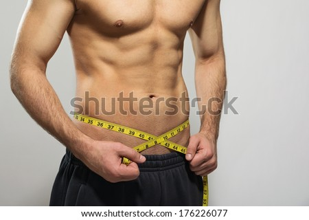 Closeup studio shot of fit muscular young Caucasian man measuring his waist. Copy space available. Sport, diet, healthy lifestyle, body care concept. - stock photo