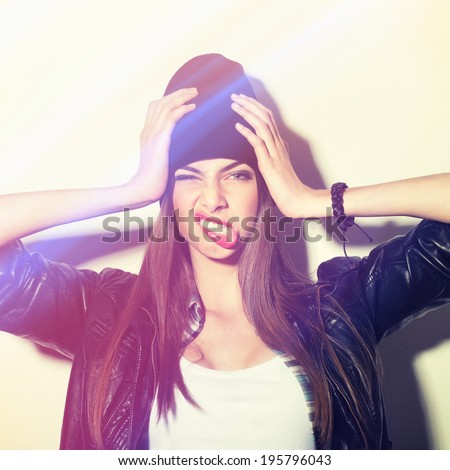 Closeup studio shot of pretty hipster teenage girl with beanie hat holding head making funny face. Square image with instant filter applied. - stock photo
