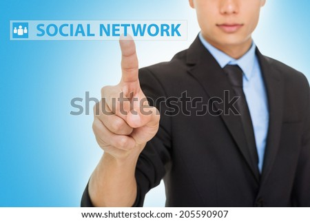 Closeup studio shot of young businessman clicking social network button against blue background. Concept. Horizontal. Selective focus. - stock photo