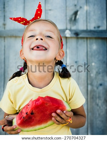 closeup summer portrait of a cute happy little girl with big red slice of watermelon - stock photo