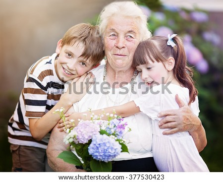 Closeup summer portrait of happy grandmother with grandchildren outdoors - stock photo