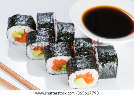 closeup sushi wrapped in nori with salmon and avocado with chopsticks and soy sauce (shallow DOF) - stock photo