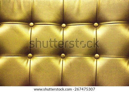 Closeup texture of vintage gold leather sofa with shadow and light . - stock photo