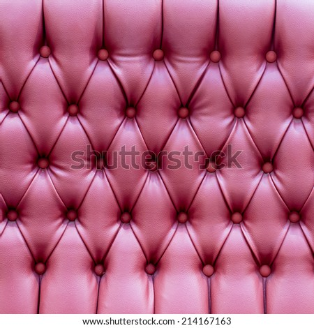 Closeup texture of vintage red leather sofa for background,Luxurious red-tone leather texture furniture with buttons - stock photo