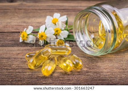 Closeup the yellow soft gelatin supplement fish oil capsule on wooden - stock photo
