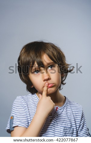 Closeup Thoughtful Young Boy Looking Up with Hand on Face Against Gray Background - stock photo