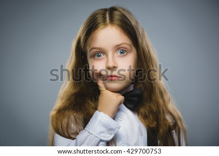 Closeup Thoughtful Young girl Looking Up with Hand at Face isolated on Gray Background - stock photo