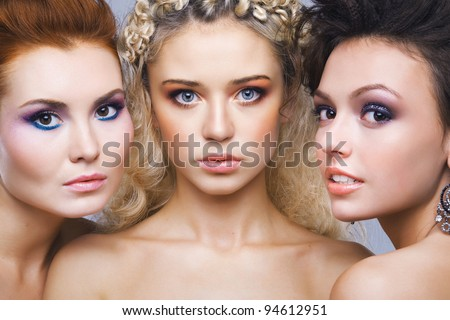 Closeup three beautiful young girls standing together - stock photo