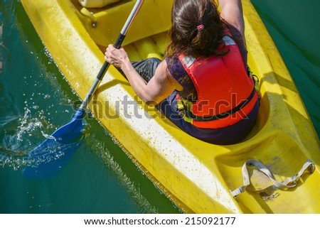 Closeup to a young girl canoeing in a yellow boat, upper shot - stock photo