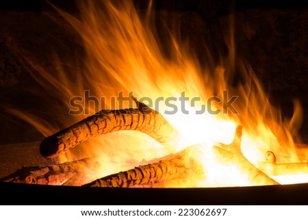 closeup to fire bowl with stack of wood - stock photo