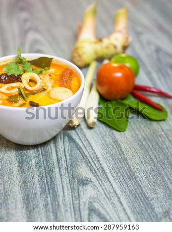 Closeup Tom Yum Kung-Thai spicy soup with Herb set of Tom Yum Soup Ingredients on wood background - stock photo