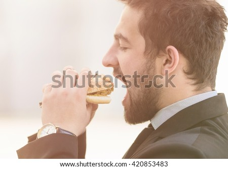 Closeup toned image of businessman eating junk food on street. Freelance man in business suit having snack before work.  - stock photo