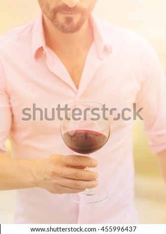 Closeup toned image of glass with red wine. Handsome professional sommelier in pink shirt holding glass with delicious red wine. - stock photo