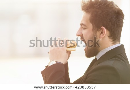 Closeup toned image of handsome businessman or freelancer eating junk food while going to work to office. Business and freelance concepts. - stock photo