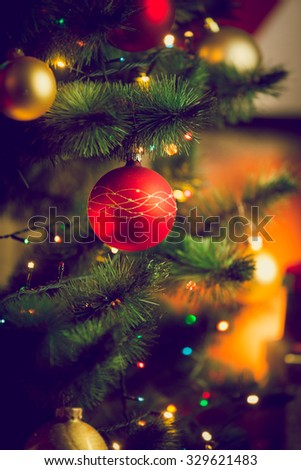 Closeup toned photo of red bauble on Christmas tree next to fireplace at living room - stock photo