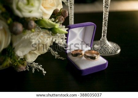Closeup toned photo of two golden wedding rings lying on table next to bridal bouquet - stock photo