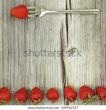 Closeup, top view, flat layout. Ripe strawberry on a fork on a worn wooden background.   - stock photo