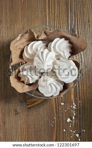 Closeup top view of lot of meringues in iron bowl on dark wooden background - stock photo