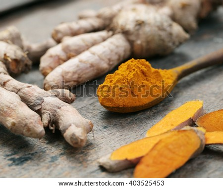 Closeup Turmeric powder and fresh turmeric roots. - stock photo