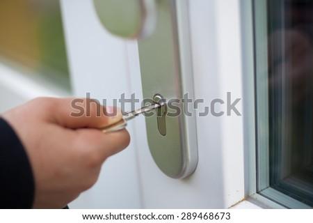 Closeup unlocking outdoor security doors (shallow DOF) - stock photo