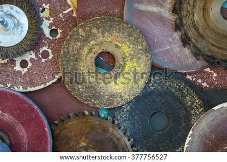 Closeup various abrasive discs, hacksaw and circular saw blades pattern.  - stock photo