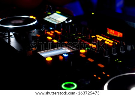 Closeup view at night of the colourful lights on the turntables and music mixing deck at a disco used by the DJ to mix and scratch audio for the dance or concert - stock photo