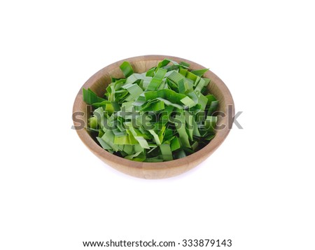 Closeup view focus on shredded pandan leaf in wooden bowl and blurring out the loose leaf at the background. The processed leaf is used as herbal tea for its sweet fragrance and medicinal benefits. - stock photo