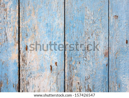 Closeup view of a grungy dilapidated blue cracking timber plank wall for textural background. - stock photo