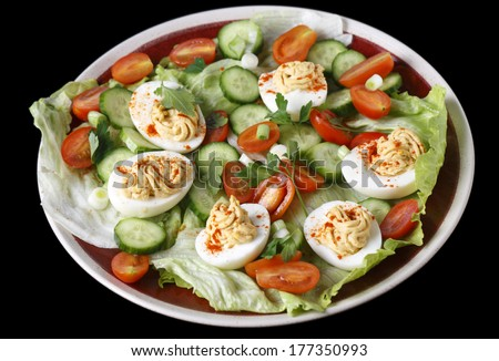 Closeup view of a salad of deviled eggs served with lettuce, miniature tomatoes, sliced cucumber and chopped green onions or scallions - stock photo