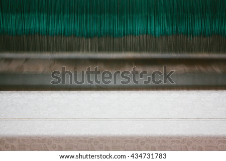Closeup view of a silk yarns being woven with a loom machine. Moving at a very high speed, the yarn looks almost abstract. - stock photo