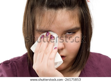 Closeup view of a young girl wiping tears from her eyes with a tissue - stock photo