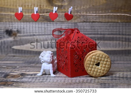 Closeup view of beautiful cupid angel decorative figurine near red paper greeting valentine box near clothes-peg in shape of heart with round pastry on wooden background copy space, horizontal picture - stock photo