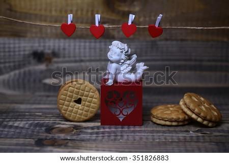Closeup view of beautiful cupid angel decorative figurine on red paper greeting valentine box near clothes-peg in shape of heart with round pastry on wooden background, horizontal picture - stock photo
