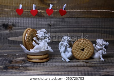 Closeup view of beautiful cupid angels decorative figurine near red paper greeting valentine clothes-peg in shape of heart with round pastry on wooden background, horizontal picture - stock photo