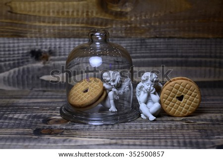 Closeup view of beautiful cupid angels decorative figurine near red paper greeting valentine clothes-peg in shape of heart with round pastry under glass flask on wooden background, horizontal picture - stock photo