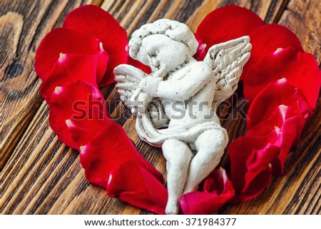 Closeup view of beautiful cupid with the trumpet, angel decorative figurine near red rose petals on wooden background. Greeting card . St Valentine's Day concept. Horizontal picture with copy space - stock photo
