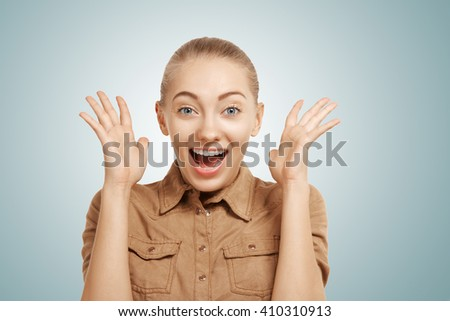 Closeup view of cheerful young blond woman crossing her fingers against blue background. Isolated portrait of happy Caucasian female hoping hard with fingers crossed. Human emotions, facial expression - stock photo