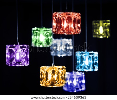 Closeup view of contemporary light fixture on a dark background. Small colorful bright lights creating a festive and romantic atmosphere. - stock photo