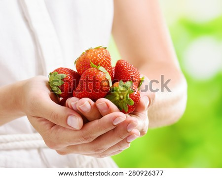 Closeup view of fresh ripe red strawberries in hands of young woman in white dress on nature background. Healthy eco sweet food rich in vitamins. Product of organic farming. - stock photo