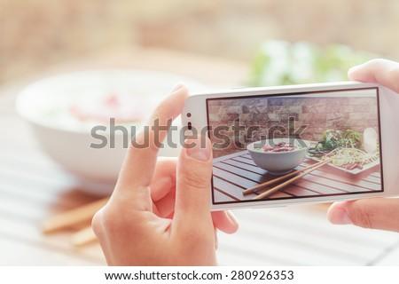 Closeup view of lifeview process on a smartphone for taking a picture of Pho Bo in street cafe in Vietnam. The Pho Bo is a traditional Vietnamese beef noodle soup. Popular healthy street food. - stock photo