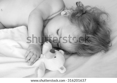 Closeup view of lovely little sleeping boy child with blonde curly hair round cheeks and tiny fingers lying with closed eyes in bed near bear toy black and white, horizontal picture - stock photo