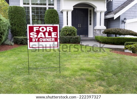 Closeup view of Modern Suburban Home for Sale Real Estate Sign in front of modern home - stock photo