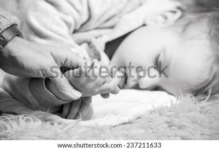 Closeup view of mother holding son's hand while he is sleeping - stock photo