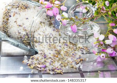 Closeup view of natural floral potpourri with a fresh aromatic scent to refresh the air in your home spilling out of a glass container onto a tiled surface with a spray of pretty delicate pink flowers - stock photo