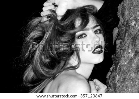 Closeup view of one attractive enigmatic glamour young woman with long hair and bright makeup with bare shoulder near tree trunk with moss in evening forest outdoor black and white, horizontal picture - stock photo