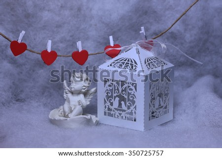Closeup view of one beautiful cupid angel decorative figurine near paper greeting valentine box and hanging red clothes-peg in shape of heart with white wadding decorating snow, horizontal picture - stock photo