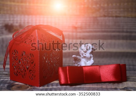 Closeup view of one beautiful cupid angel decorative figurine near red paper greeting valentine box in shape of heart near silk ribbon bow with no people on wooden background, horizontal picture - stock photo