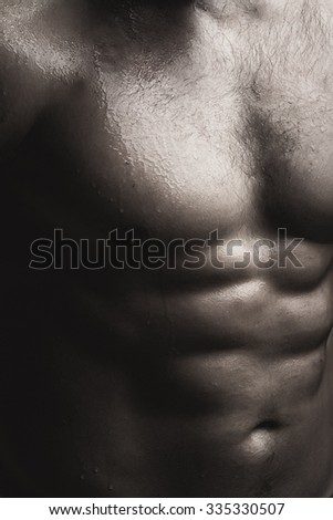 Closeup view of one handsome sexual strong young male bare chest of muscular wet body standing posing on studio background black and white, vertical picture - stock photo
