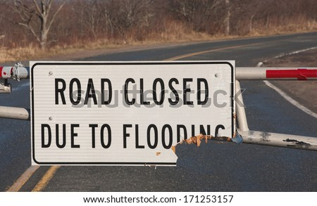Closeup view of road closed due to flooding sign. - stock photo
